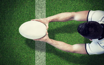 AFL Player Holding Ball against pitch with line